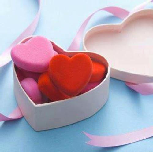 هدية على شكل قلب تحوي عدة أشكال قلوب مختلفة الألوان